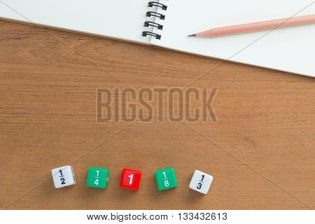 Color fraction dices blank white notebook and a pencil on wooden desk with copyspace for text