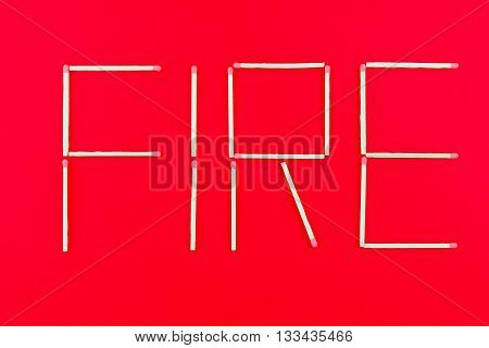 Written fire made with matchstick on red background