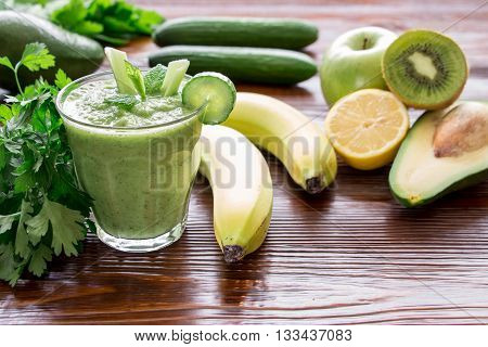 Left glass of green vegetable smoothie near ingredients celery avocado cucumber kiwi apple banana lemon and herbs on wooden background. Green vegetable smoothie and ingredients. Horizontal.