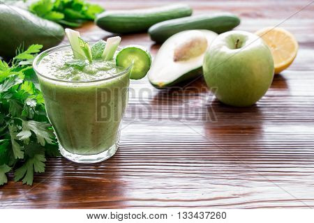 Left glass of green vegetable smoothie near ingredients celery avocado cucumber apple lemon and herbs right empty space on wooden background. Green vegetable smoothie and ingredients. Horizontal.