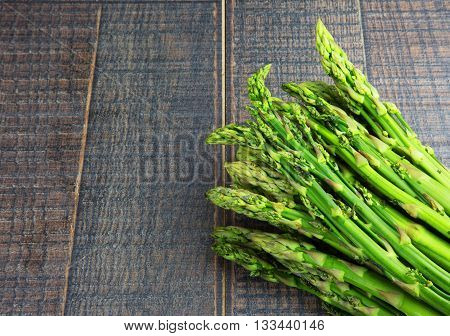 A bunch of fresh green asparagus on wooden background with empty space for text on the right. Flat top view. Horizontal.