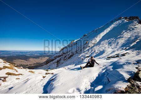 Yoga session in beautiful slovakian Belianske Tatry mountains. Beautiful sunny panorama - Siroka dolina - wide valley in snow - Ardha-Matsyendrasana half spinal twist