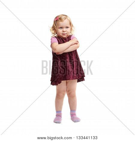 Young little girl with curly hair and crossed arms in purple dress standing over isolated white background