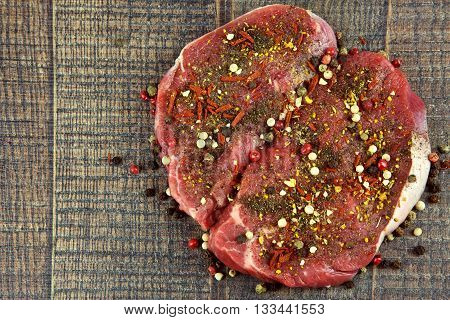 Two raw sirloin steaks sprinkled with spices on wooden background flat view from above