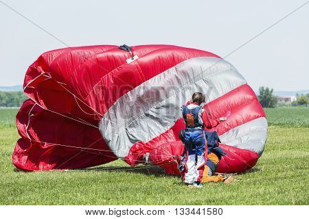 Skydiver with red parachute after landing on the ground.
