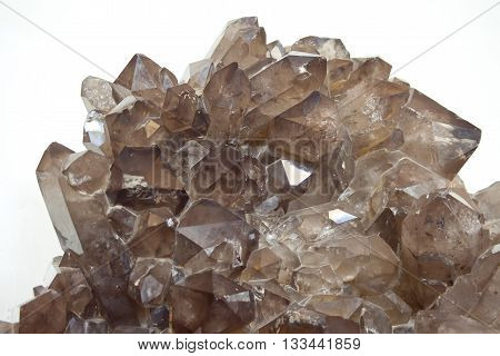 Cluster of smokey quartz crystals on white. Close up