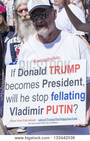 SAN DIEGO USA - MAY 27 2016: A white male holds a slightly vulgar sign at an anti-Trump protest outside a Trump rally in San Diego.