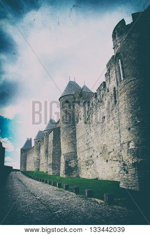 Vintage and dusty effect. Rock road between dubble antique stone wall of heritage city name Carcassonne the town fortress in France