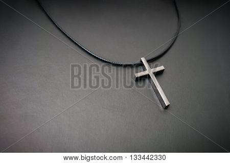 Necklace With Metallic Cross On Dark Background.