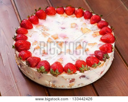 Cake with strawberries gelly yogurt and cherries shot from above over wooden table. Full length