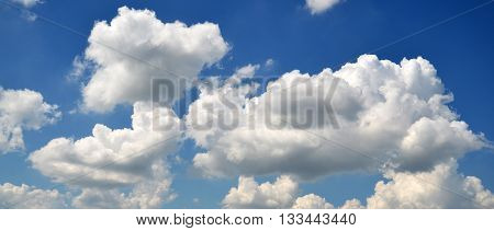 White clouds flying in deep blue summer sky