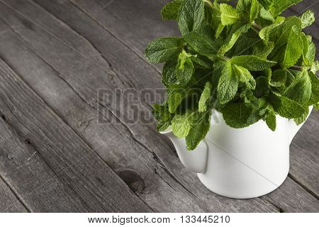 Mint Branches In Teapot On A Dark Wooden Background