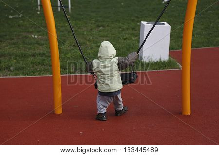 Little child in autumn jackets swinging in a swing outside in playground