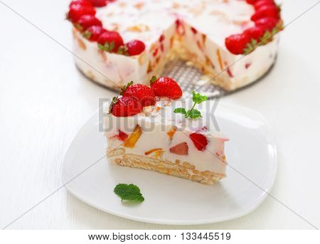 Cake with strawberries gelly yogurt and cherries shot from above. Isolated on white background. One piece in a white plate