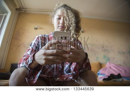 Young girl beauty Redhead woman writing message on cell phone at home. Looking down