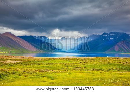 Smooth water of the cold lake reflects clouds. Cold summer in Iceland