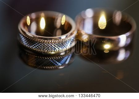 wedding rings on the glass table in black and white. Gold.
