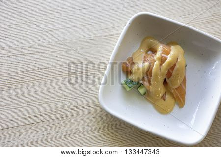 japanese food salmon with  mayonnaise in a smaill disc and wood background