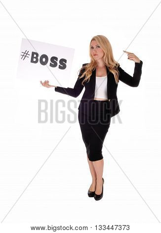 A beautiful young blond woman in a black business suit standing isolated for white background holding a sign #BOSS up.
