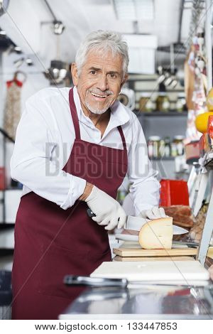 Happy Salesman Slicing Cheese In Store
