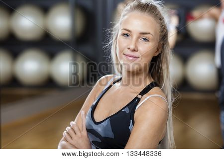 Confident Woman Standing Arms Crossed In Gym