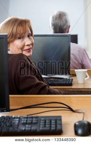 Portrait Of Smiling Senior Woman Sitting In Computer Class