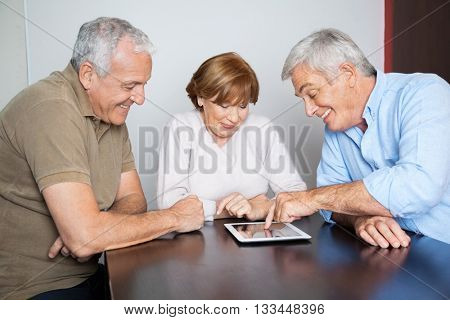 Senior Classmates Watching Man Using Digital Tablet At Desk