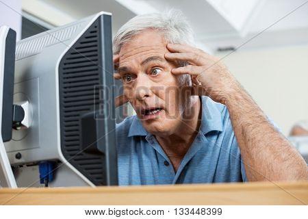 Stressed Senior Man Looking At Computer Monitor