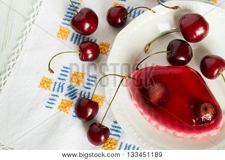 Fruity a jelly on a plate and fresh sweet cherries on a napkin on a light wooden background.