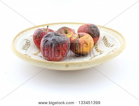 Rotten apple on plate, uneatable, unhealthy apple