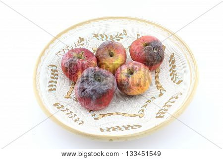 Rotten apple on decorative plate, putrid apple