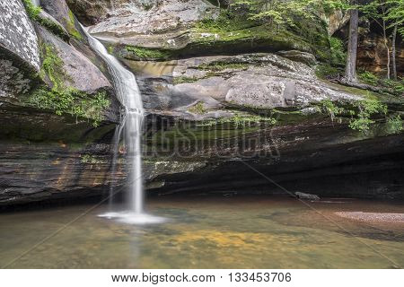 Cedar Falls a beautiful waterfall in the Hocking Hills of Ohio cascades down a sandstone cliff before finally plunging into a pool below.