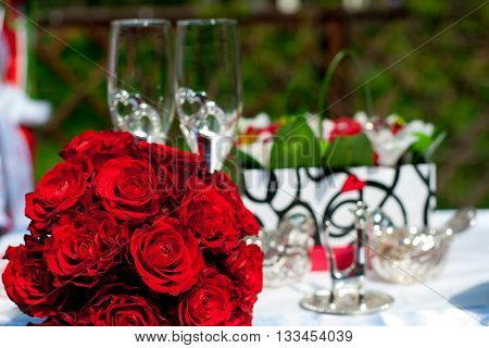 wedding bouquet of red roses on a background of accessories for the wedding