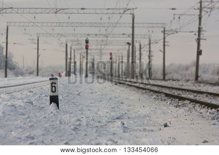 Electrified railway tracks with red railway signals - railway station with traffic sign in winter period