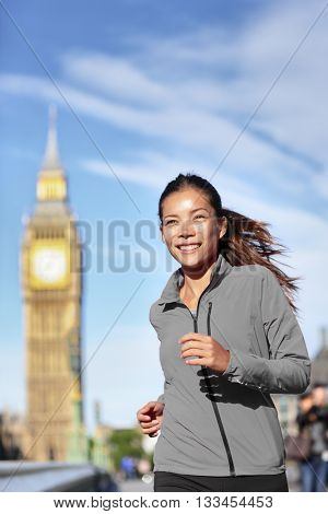 Healthy city lifestyle fitness runner woman. Cute Asian girl in grey windbreaker jacket running in London with Big Ben in the background, exercising cardio living a fit active life.