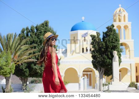 Santorini island Greece travel. Happy tourist woman walking in Oia village visiting blue dome church during summer vacation holidays. Beautiful young adult in fashion sun hat and red dress.