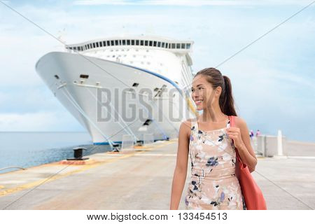 Cruise Ship Vacation Happy Female Tourist on Pier. Smiling happy young woman walking on pier by huge cruise ship moored at jetty. Beautiful woman in casuals is enjoying her vacation.