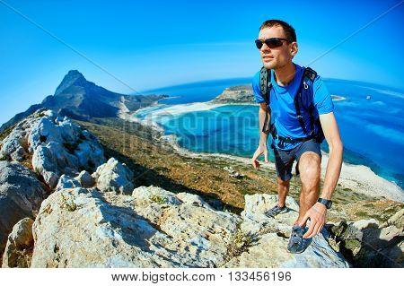 man runs on a rock against a blue sea