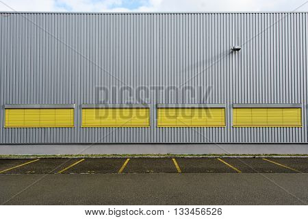 Industrial building wall background with yellow blindes and vertical and horizantal lines