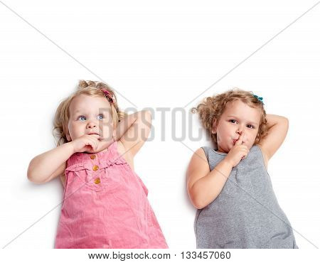 Couple of young little girls sinsters with in gray and pink dress lying and doing shh silence sign over isolated white background
