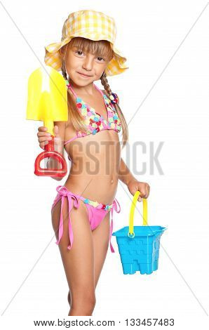 Adorable little girl standing in swimming wear and panama hat with bucket and spade, isolated on white background