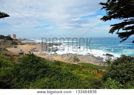 View onto the ocean outside of Pablo Nerudas house right at the beach with green trees in the foreground