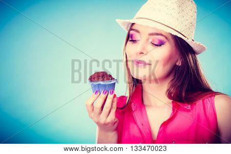Sweet food sugar make us happy. Smiling woman summer clothing holds cake chocolate muffin in hand blue background