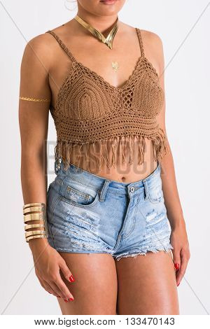 Closeup of female model's body in brown crochet fringes crop top and denim shorts. No retouch