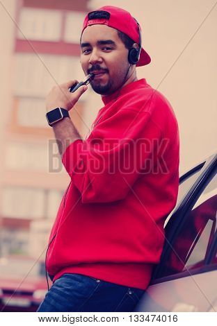 Young Black Guy Smoking E-cigarette Vaporizer Leaning On Car