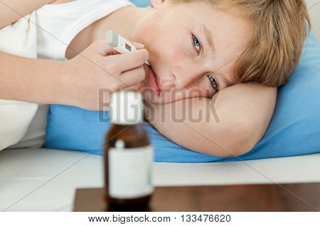 Boy Using Thermometer With Medicine Bottle Nearby