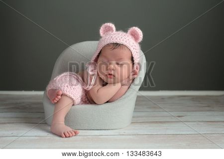A two week old newborn baby girl sleeping in a little chair. She is wearing a crocheted pink bear bonnet and matching shorts. Shot in the studio on a gray background.