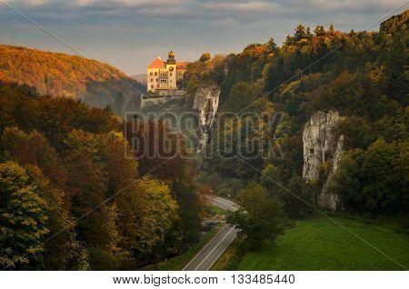 Sunrise at Pieskowa Skala Castle among autumn trees Poland