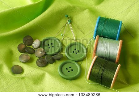 A collection of haberdashery items with a green theme - buttons dressmaker's pins and cotton on bobbins. All on a piece of green fabric.