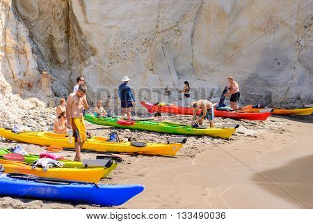 MELOS GREECE - SEPTEMBER 4 2012: People with kayaks pulled out on the shore of Gerontas beach off the south coast of Melos island.